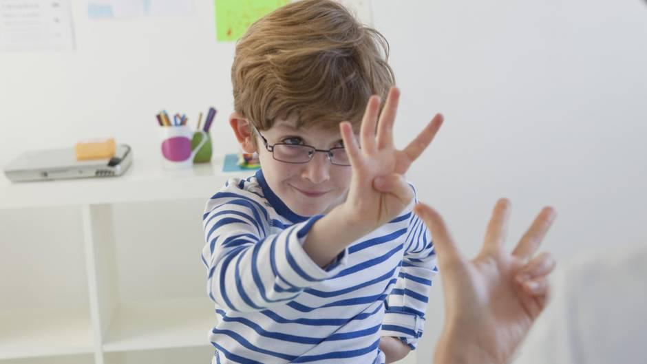 Ein kleiner Junge übt das Zählen mit den Fingern