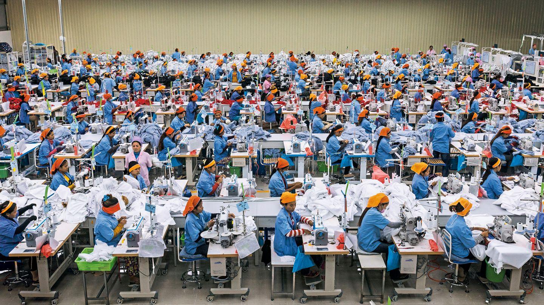 Einfache Näherinnen tragen orangefarbene Kopftücher, ihre Aufseherinnen lila. In der Textilfabrik Seduno am Stadtrand von Phnom Penh produzieren sie auch für C&A und H&M.