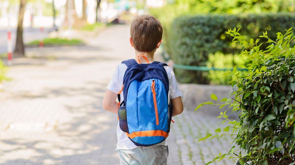 Ein Junge mit Schulranzen auf dem Rücken