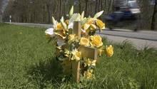 Ein mit Blumen geschmücktes Kreuz am Straßenrand