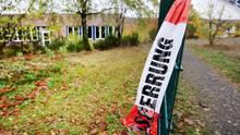 """An einem grünen Drahtzaun hängt ein Ende eines rot-weißen Flatterbandes mit """"Polizeiabsperrung"""" darauf"""
