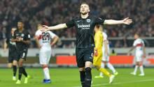 Mit ausgebreiteten Armen und den Augen zum Himmel geht Ante Rebic im schwarzen Truikot von Eintracht Frankfurt über den Platz