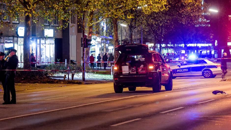 Mitten auf einer mehrspurigen Straße in Hamburg steht ein schwarzer Jeep mit offener Heckklappe. Im Hintergrund ein Polizeiauto