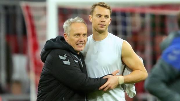 Arm in Arm stehen Freiburgs Trainer Christian Streich und Bayerns Torwart Manuel Neuer auf dem Platz. Streich hat Neuers Trikot