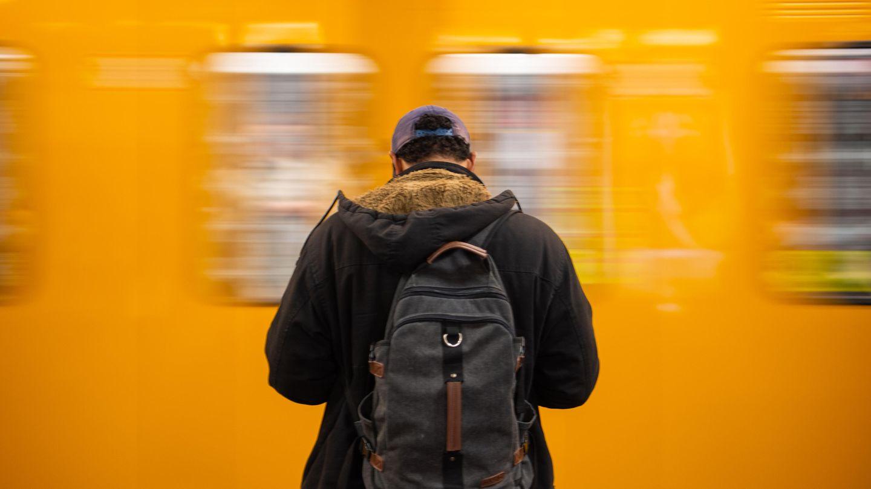 Ein Mann steht vor einer gelben U-Bahn in Berlin