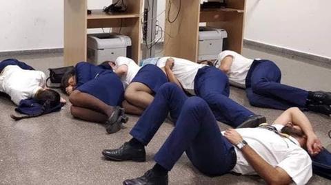 Ryanair-Mitarbeiter liegen auf dem Boden eines Flughafenbüros