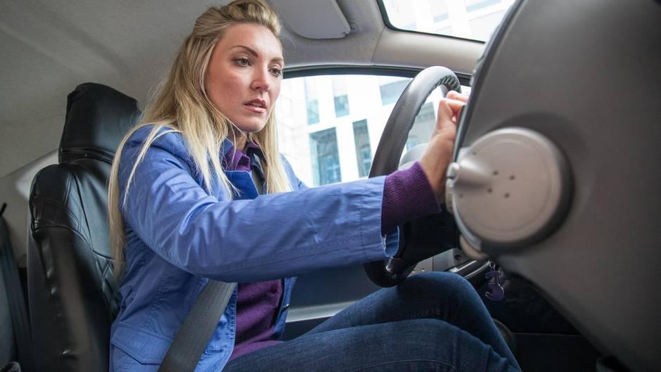 Frau schaltet Autoradio ein
