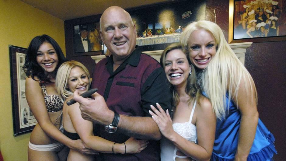 Dennis Hof in der Mitte, umgeben von jungen Frauen
