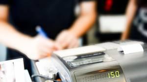 Mitarbeiter notiert etwas hinter einer Kasse