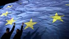 Zwei Personen recken vor einer EU-Flagge ihre Faust in die Höhe