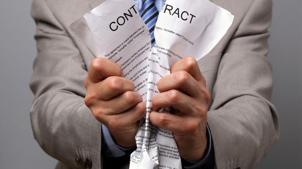 Ein Mann zerreißt einen Vertrag