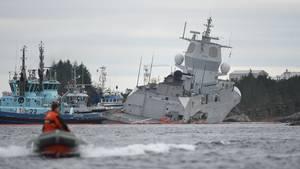 Ein norwegisches Kriegsschiff liegt vor dem felsigen Strand, rechts hinten liegt es tief im Wasser
