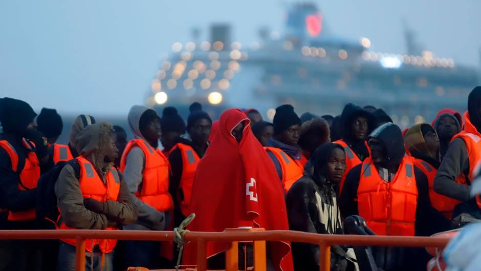 In rote Decken und Schwimmwesten gehüllte Migranten stehen nach ihrer Ankunft im Hafen von Malaga in Spanien. Viele Migranten, die übers Mittelmeer kommen, wollen nach Deutschland.
