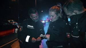 ist Polizeihauptkommissar Dirk Schröder undPolizeioberkommissar Norbert Faust im Gespräch mit einer Kollegin, die ihnen eine Personenbeschreibung gibt.