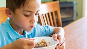 Ein Junge am Frühstückstisch