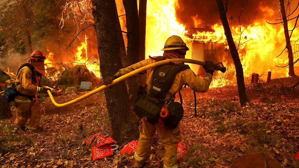Feuerwehrleute bekämpfen die Flammenin Magalia, Kalifornien