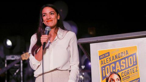 Alexandria Ocasio-Cortez steht auf der bühne und hält ein Mikrofon in der Hand