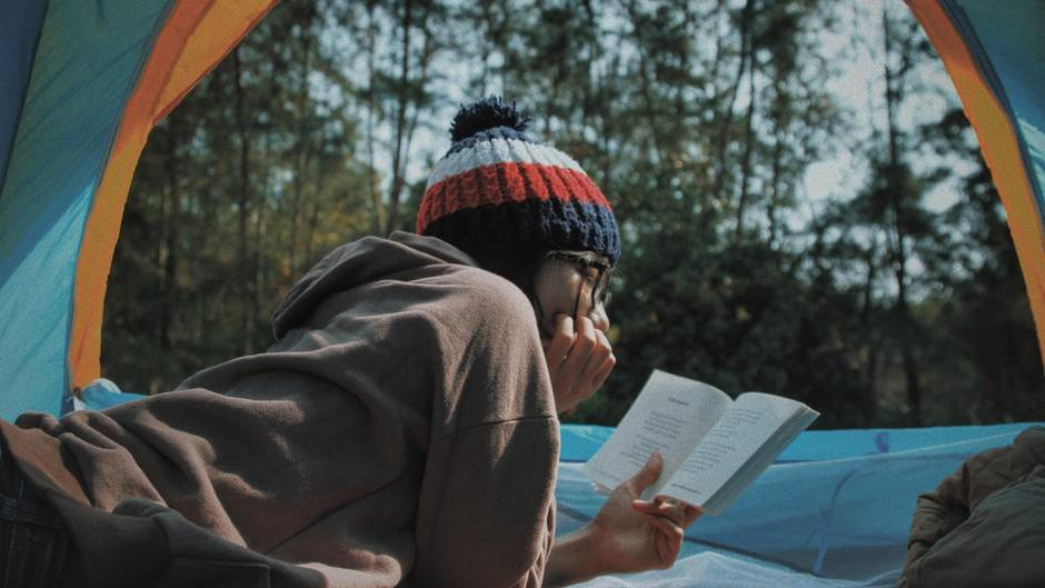 Person liest draußen ein Buch