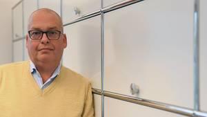 Ralf Zietz lehnt an einem Schrank in seinem Büro