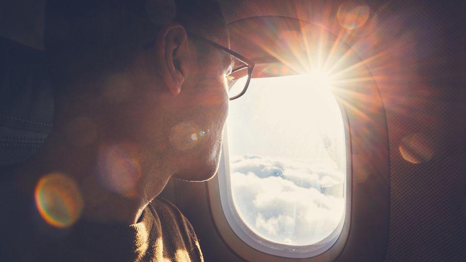 Ein Mann schaut durch ein Flugzeugfenster nach draußen, während die Sonne nach drinnen scheint