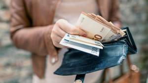 Eine Frau in hellbrauner Lederjacke zieht etliche Euroscheine aus ihrem großen Portemonnaie