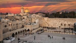 In Jerusalem geht über Felsendom und Klagemauer die Sonne unter. Der Himmel ist orangerot gefärbt