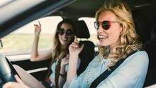 Zwei Frauen sitzen bei Sonne in einem Auto und scheinen während der Fahrt bei offenen Fenstern mit dem Radio mitzusingen