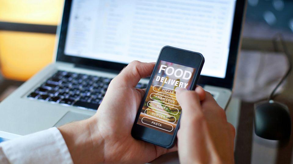 Ein Mann hält ein Smartphone mit der Seite eines Bringdienstes in den Händen, dahinter steht ein Laptop mit Mail-Eingang
