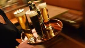 Kellnerin trägt Bier zum Gast