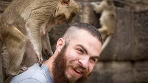 Ein Tourist spielt in Thailand mit einem Affen
