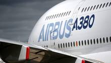 """Auf einem weißen Flugzeug steht in zwei unterschiedlichen Blautönen """"Airbus A380"""" auf der Seite"""