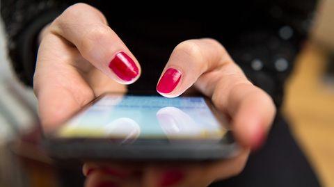 Frauenhände tippen auf ein Smartphone-Display