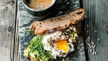 Avocado auf Röstbrot mit Nüssen, Sonnenblumenkernen, Ei, Kresse, Ducca und Kaffee