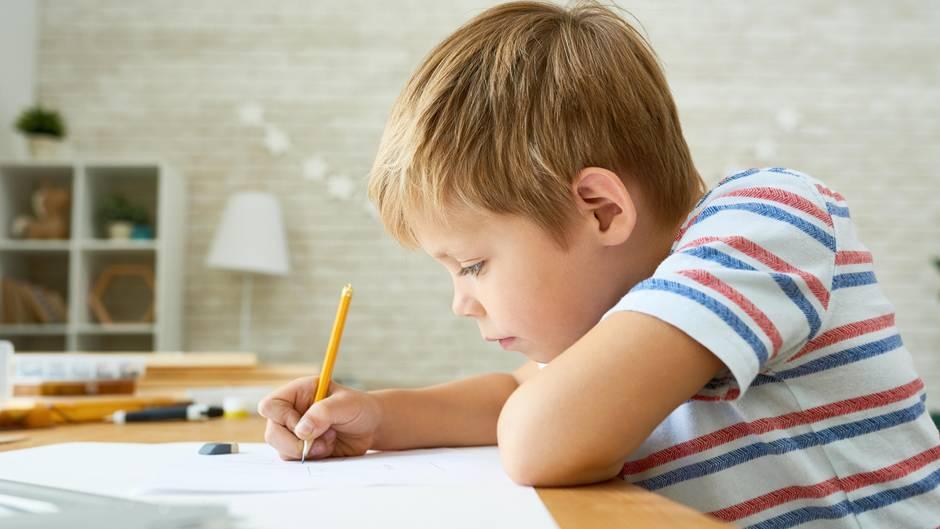 Junge schreibt Brief