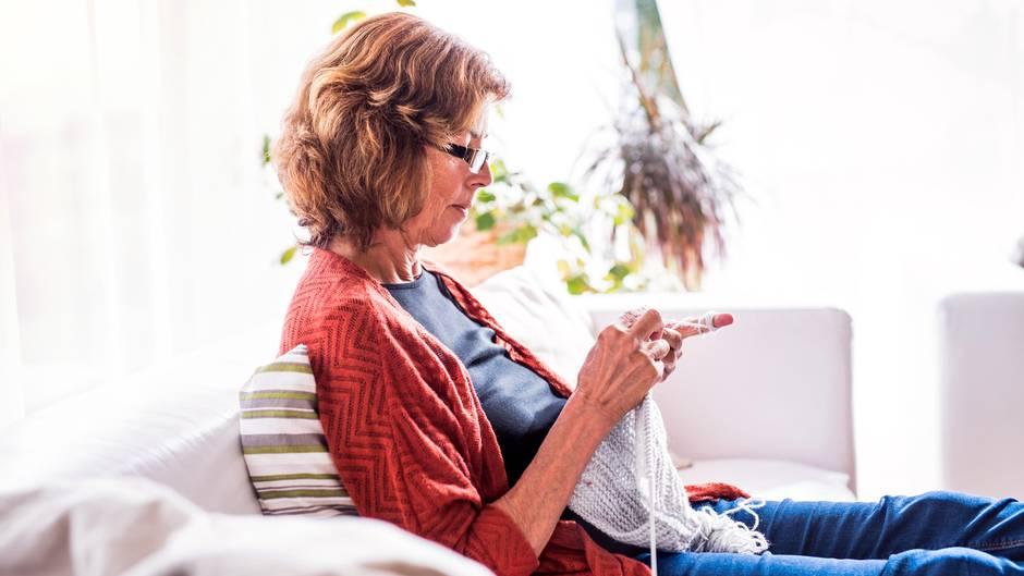 Eine Frau sitzt auf dem Sofa uns strickt