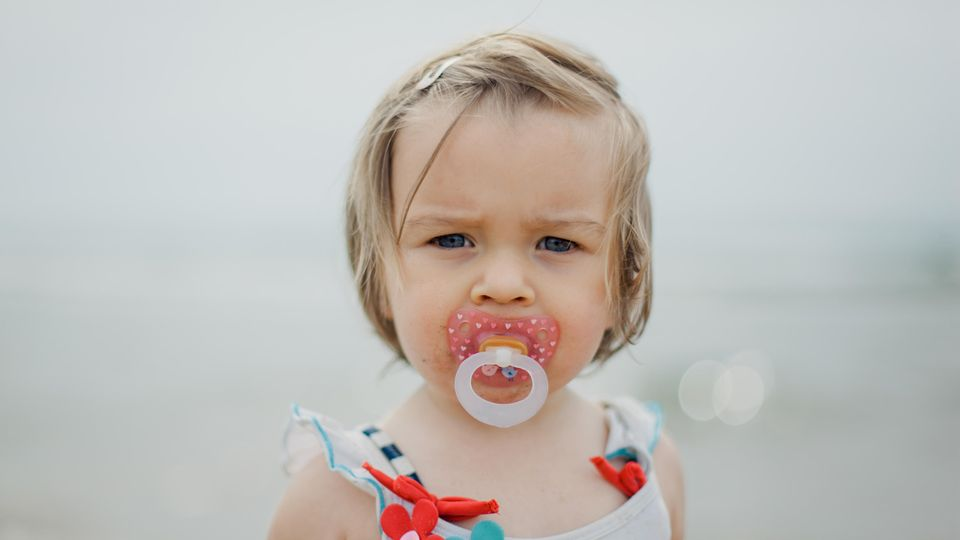 Ein Kind hat einen Schnuller im Mund