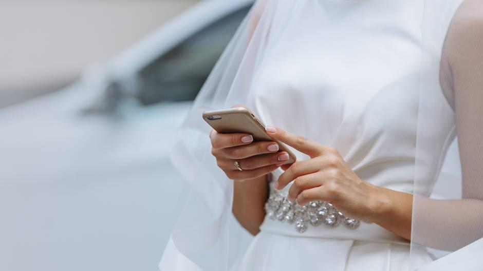 Eine Braut tippt auf dem Handy