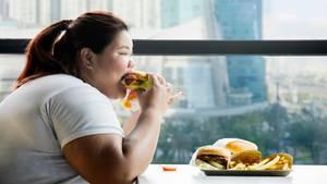 Eine übergewichtige Frau isst Burger und Pommes