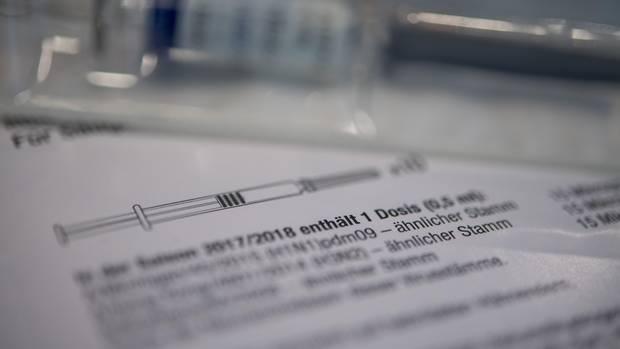 Eine Spritze mit Grippe-Impfstoff liegt auf einem Tisch