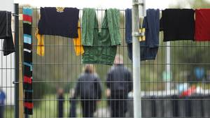 In einer Flüchtlingsunterkunft hängt Wäsche zum Trocknen über den Zaun