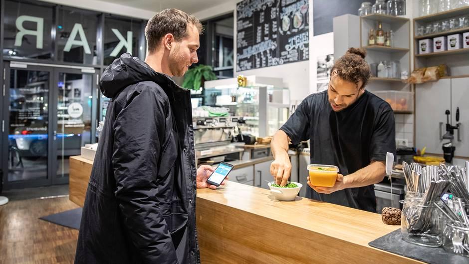 """Mit der App """"Too Good To Go"""" verkauft Gastronom Jérôme Bah (r.), was übrig blieb und sonst im Müll landen würde, bevor er sein Café für diesen Tag schließt"""