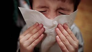 Ein Junge hält ein Taschentuch vor sein Gesicht