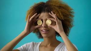 Frau hält Münzen vor ihre Augen