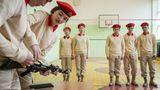Jungarmisten bauen in der Turnhalle ihrer Schule ein Kalaschnikow-Modell auseinander.