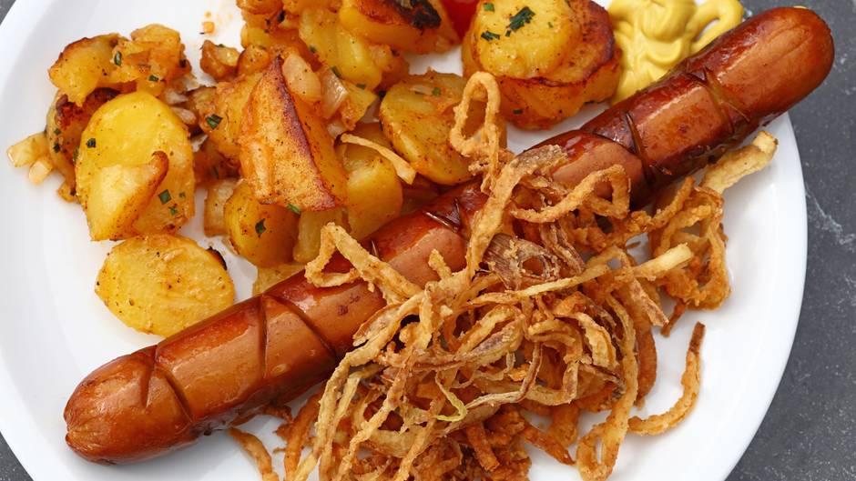 Auf einem Teller liegen Wurst und Bratkartoffeln