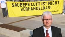 """Jürgen Resch, einer der Geschäftsführer der Deutschen Umwelthilfe, im September vor Beginn einer Verhandlung über Diesel-Fahrverbote. Im Hintergrund ein Greenpeace-Plakat mit der Aufschrift """"Saubere Luft ist nicht verhandelbar""""."""