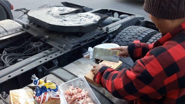 Dieseltank statt Küchenzeile: Einer der Filipinos hackt Hähnchenfleisch
