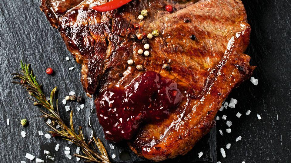 Es ist serviert: ein Steak, garniert mit Chili, Pfeffer, Rosmarin. Lecker und nahrhaft. Fleisch enthält wichtige Mineralien