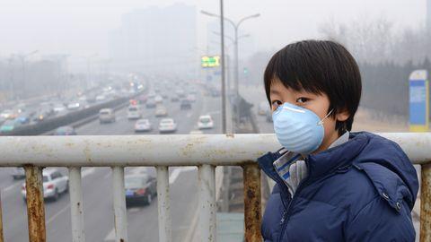 Ein junge steht auf einer Brücke im Smog. Er trägt eine Atemschutzmaske