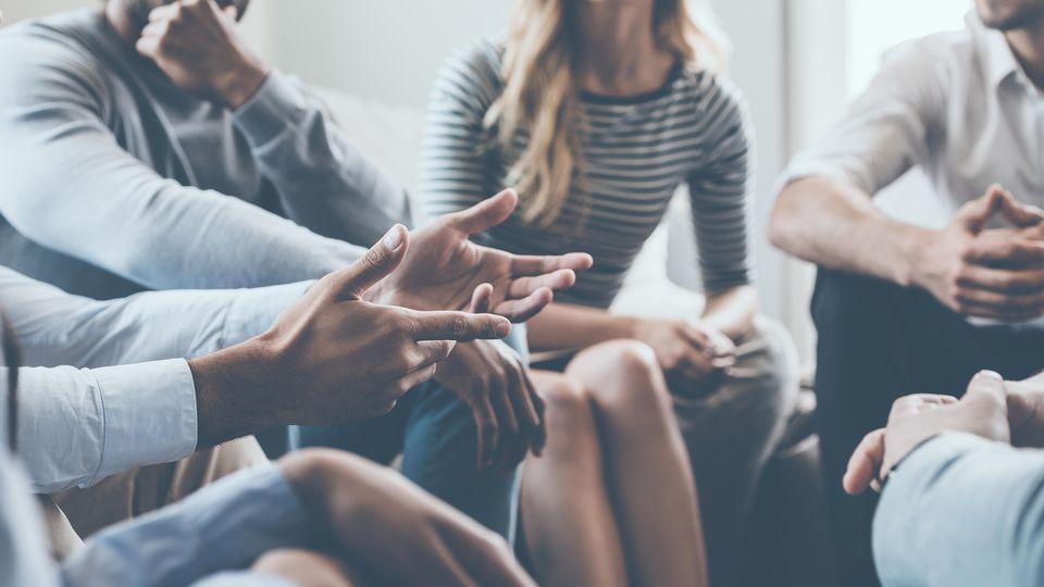 Einige Personen sitzen im Kreis im Rahmen einer Gruppentherapie zu Burn-out